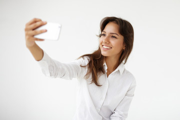 Beautiful young Latin woman office worker wearing white shirt taking selfie using smart phone. Student girl smiling broadly at front camera of her mobile for self portrait. Modern technologies concept