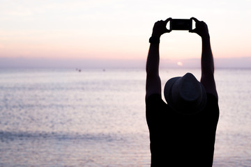 man taking photos of sunset with mobile phone.