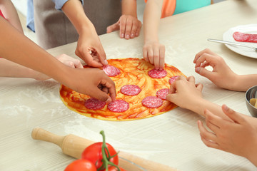Group of children preparing pizza during cooking classes