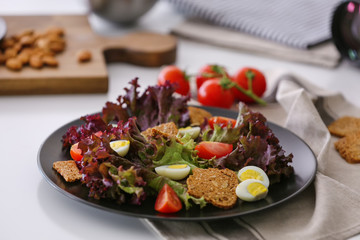 Salad with cherry tomatoes and quail eggs served on black plate, closeup