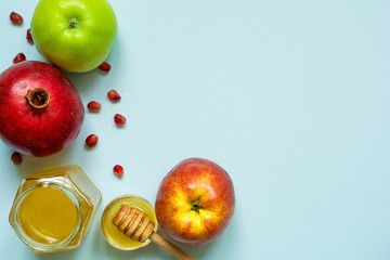 Honey, apple and pomegranate for Rosh Hashanah on blue background