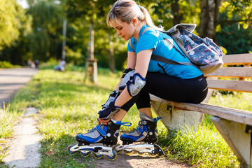 Athletic woman sitting on a bench in a park and putting on inline skates. Close up. Sport lifestyle.