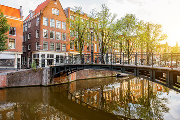 Morning view on the beautiful buildings and water channel in Amsterdam