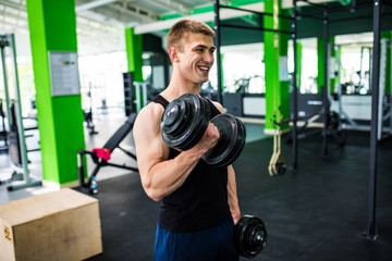 very power athletic man , execute exercise with dumbbells, in gym