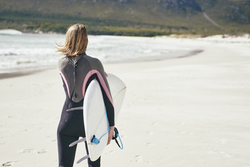 Single female surfer walking along the beach with her surfboard