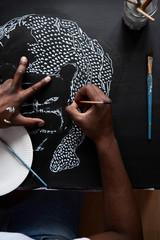 Overhead of person wearing cap and white t-shirt painting tiger with white colour on black paper.