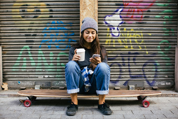 Portrait of a skater girl chatting on phone sitting on her longboard in the city.