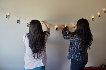 teenagers hang pictures on lighted string
