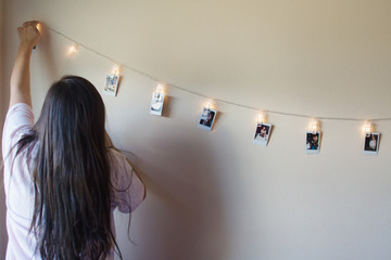 teenager hangs  pictures on lighted cord
