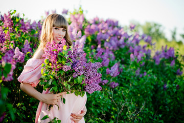 The young beautiful pregnant woman is near a big  lilac bush with a lilac bouquet in her hand