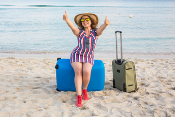 Beautiful young lady with a blue suitcase showing thumbs up gesture on the beach. People, travel, vacation and summer concept