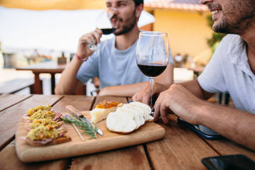 Two men drinking wine and having cheese and appetisers while wine tasting