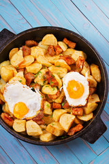 Pan-fried potato, eggs and meat. View from above, top studio shot