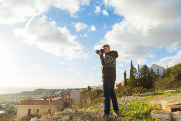 Travel, vacation, photographer and hitchhiker concept - traveler man photographed mountains and town