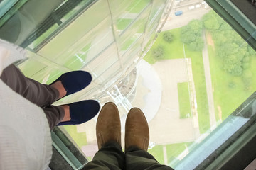 Male and female feet on a glass floor at the Ostankino tower in Moscow, Russia