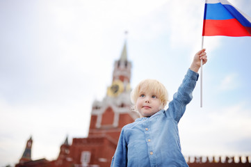 Cute little boy with russian flag with Spasskaya tower Russia, Moscow on background