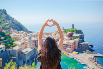 Beautiful girl making with hands heart shape on the old coastal town background of Vernazza, Cinque Terre National Park, Liguria, Italy ,Europe