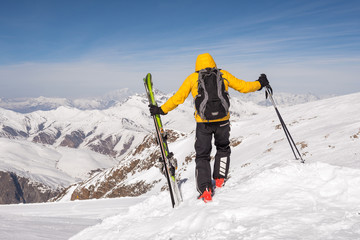 Skier walking through snow holding his skis and poles