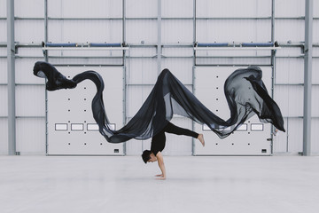 A dancer lifts himself up into a headstand as black silk ripples above him