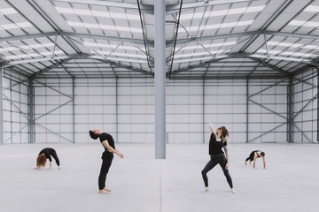 Four dancers exploring movement in a spacious empty warehouse
