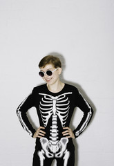 A young woman in the Skeleton costume on the white brick backgroun