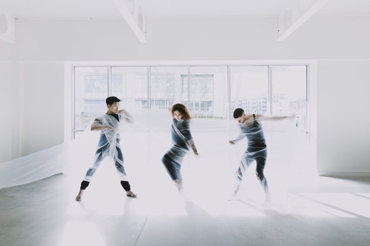 Three dancers tangled in cellophane, moving in front of a bright window