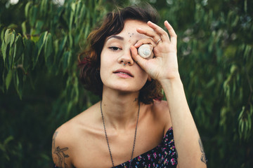 Beautiful bohemian woman holding a snail shell