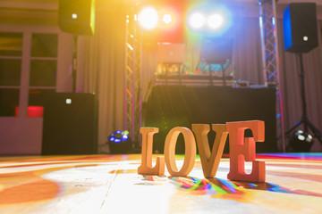 """Hölzerndes Schild """"Love"""" auf einer Tanzfläche von einem DJ nach der Hochzeitsfeier"""