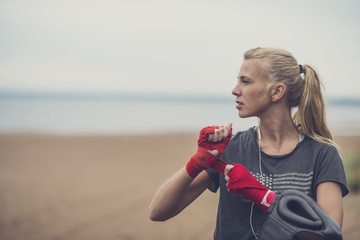 Garden Poster Martial arts Young sporty blonde woman standing in a boxing stance wrapping her wrists before the boxing training