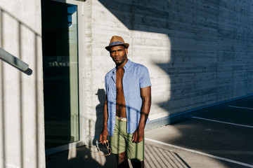 Stylish black man posing at street