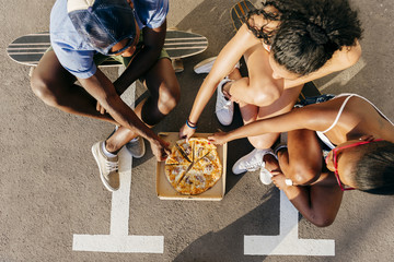 Youngsters eating pizza at street