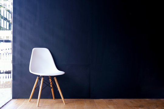 White chair in interior room  with dark blue wall.