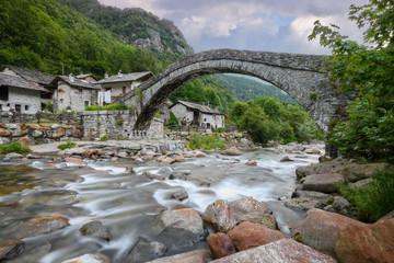 Silk effect waterfall and old (stone, Romanesque) bridge,Fondo, Valchiusella, Piedmont, Italy