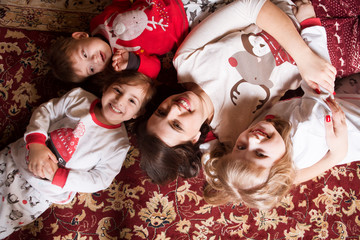 Happy family mother andand three her small children having fun lying  on a carpet.  Winter holiday Xmas and New Year.