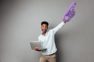Happy young african man holding laptop computer and foam finger