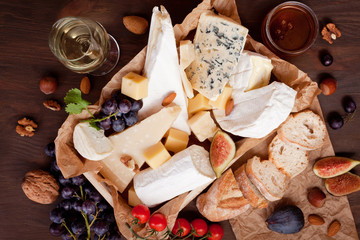 Variety of different cheese with wine, fruits and nuts. Camembert, goat cheese, roquefort, gorgonzolla, gauda, parmesan, emmental