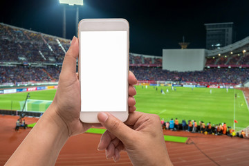 Female hand holding mobile smart phone touch screen on blurred of action photographer taking photo at player in Abstract blurred photo of soccer stadium, sport background concept
