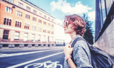 young beautiful woman with a short haircut and a backpack stands on the background of a road and buildings in the city