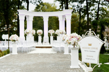 White board with lettering 'Wedding empire' stands on the path to the altar