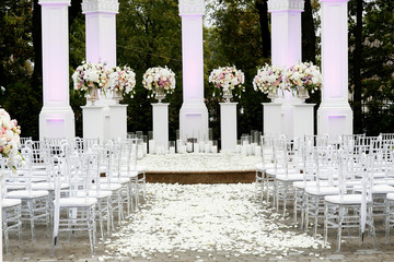 White petals cover path to wedding altar made of white pillars and bouquets of roses