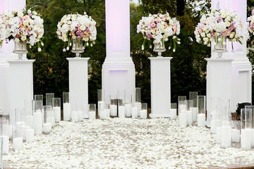 White pillars with bouquets on top and burning candles surround pavement covered with rose petals