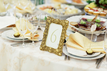 Number 6 put in a golden frame stands among white plates on dinner table