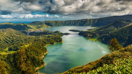 Spoed Fotobehang Olijf Establishing shot of the Lagoa das Sete Cidades lake taken from Vista do Rei in the island of Sao Miguel, The Azores, Portugal. The Azores are a hidden gem holiday destination in Europe.