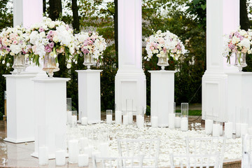 Circle among white pillars covered with rose petals