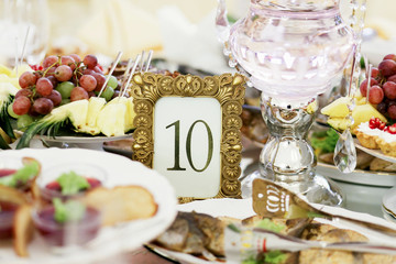 Number 10 put in a golden frame stands among white plates with fish and fruits