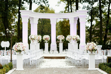 Two pillars stand before the lawn with chairs and bouquets of roses prepared for wedding ceremony