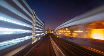 A railway track and skyscrapers seen through a long exposure motion blur in London, England, UK during early evening
