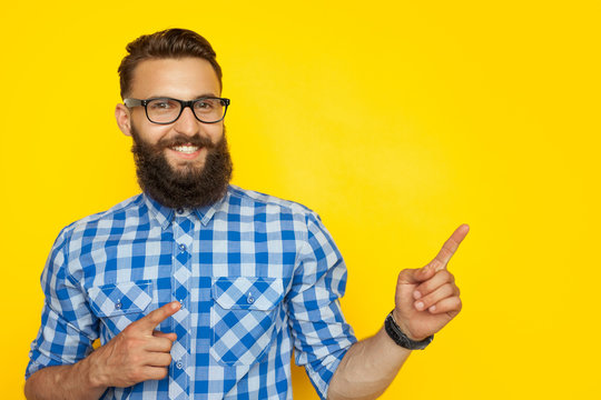 Cheerful hipster pointing on side