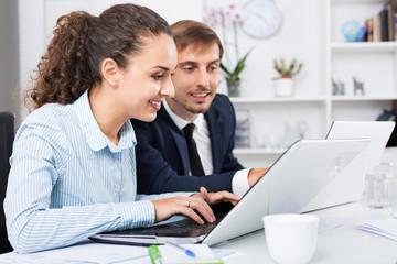 Glad business female assistant wearing formalwear using laptop
