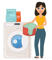 Housewife washes clothes in the washing machine. Pretty woman doing domestic work.